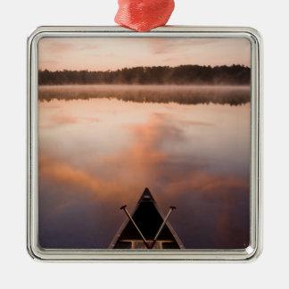 Un canoë se repose sur le rivage du lac ornement carré argenté