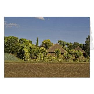 Un champ cultivé devant des maisons de toit carte de vœux