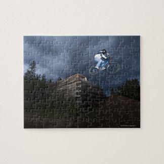 Un cycliste de montagne saute outre d'un cabine de puzzle