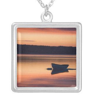 Un skiff au lever de soleil dans la portée pendentif carré