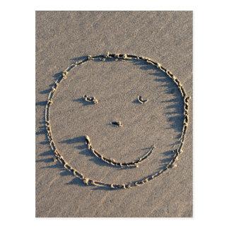Un visage souriant dessiné en sable cartes postales