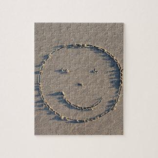 Un visage souriant dessiné en sable puzzle