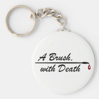 Une brosse, avec le porte-clés de logo de la mort