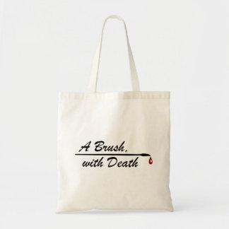 Une brosse, avec le sac fourre-tout à la mort
