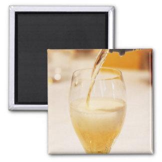 Une cannelure en verre de champagne étant remplie  magnet carré