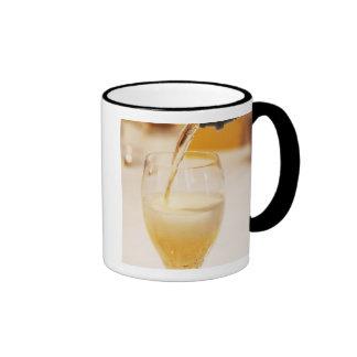 Une cannelure en verre de champagne étant remplie mug ringer