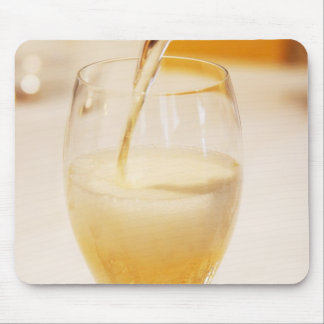 Une cannelure en verre de champagne étant remplie  tapis de souris