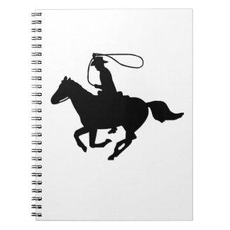Une équitation de cowboy avec un lasso. carnet à spirale