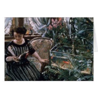 Une femme lisant près d'un réservoir de poisson carte de vœux