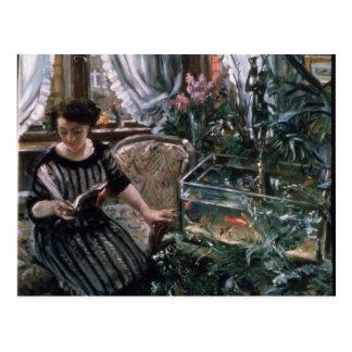 Une femme lisant près d'un réservoir de poisson cartes postales