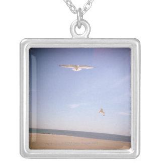 une image rêveuse des mouettes volant à la plage pendentif carré