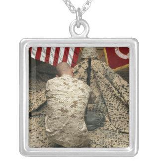 Une marine se met à genoux avant le fusil pendentif carré