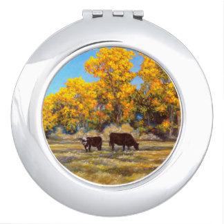 Vache et veau dans le miroir compact d'arbres d'or