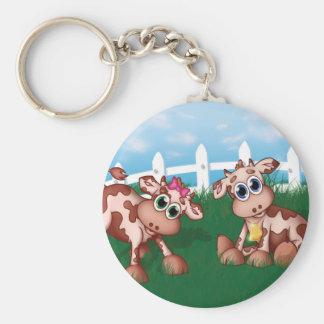 Vaches à bébé d'un côté de colline avec de porte-clé rond