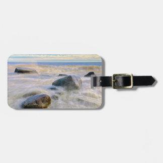 Vagues se brisant sur des roches de rivage étiquettes bagages