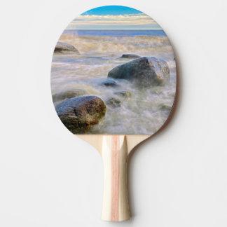 Vagues se brisant sur des roches de rivage raquette tennis de table
