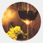 Verre de vin et de raisins verts dans la lueur adhésifs ronds