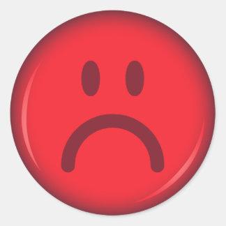 Visage souriant fâché pouty malheureux rouge sticker rond