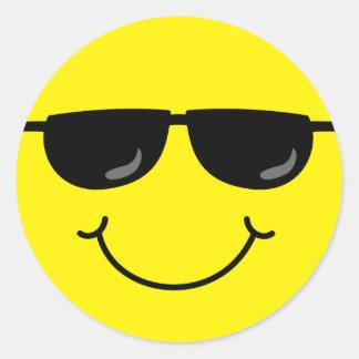 Visage souriant frais avec des lunettes de soleil sticker rond