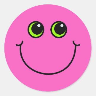 Visage souriant rose sticker rond
