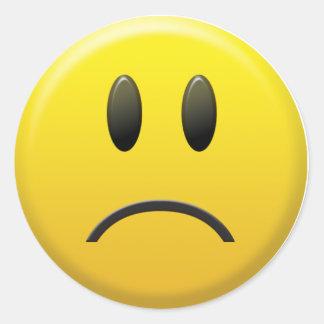 Visage souriant triste sticker rond