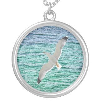 Vol de mouette au-dessus d'une mer pendentif rond