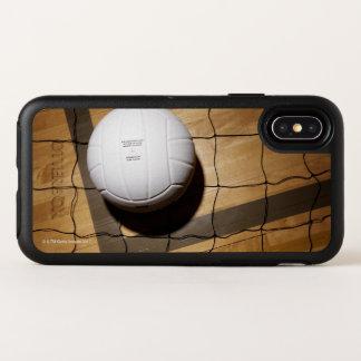 Volleyball et filet sur le plancher en bois dur