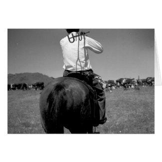 Vue arrière d'un cowboy sur un cheval avec deux carte de vœux