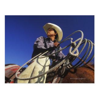 Vue d'angle faible d'un cowboy montant un cheval, carte postale
